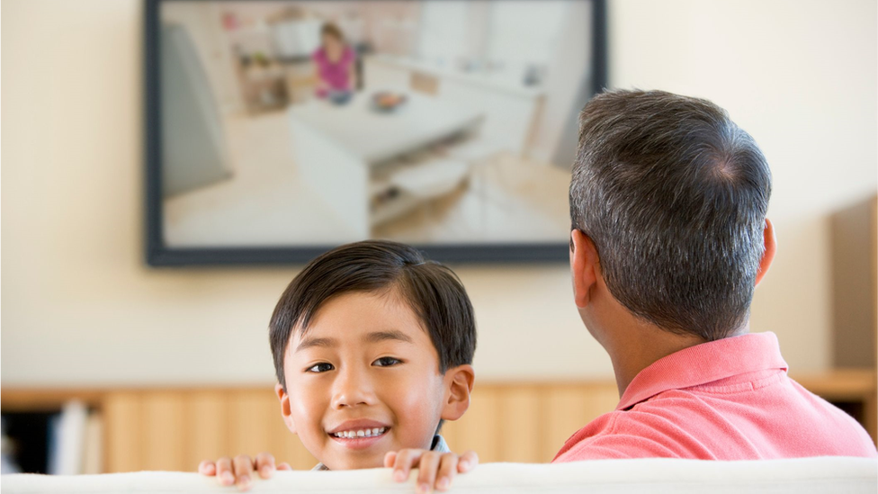 Kid looks at the camera while his father watches the screen