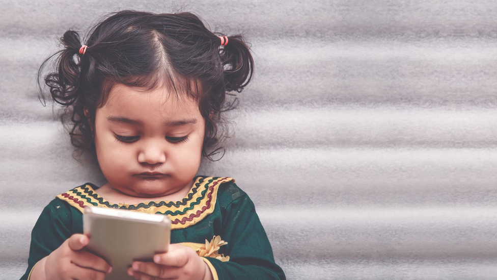Toddler playing with a mobile phone